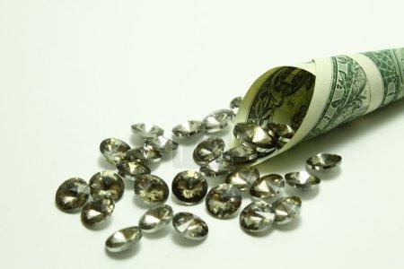 Photo pour Diamants placers qui débordent du dollar sur un fond gris - image libre de droit