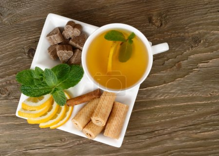 Cup of green tea, lemon, mint, cinnamon and wafers on a white square plate on a wooden background.