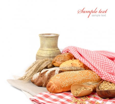 Fresh fragrant home-made bread under a checkered napkin and a jug with milk on a white background.