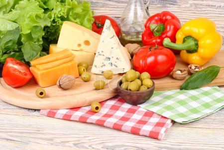 Photo for Cheese of various grades, fresh vegetables and olives on a light wooden background. Ingredients for preparation of the Italian vegetarian pizza. - Royalty Free Image