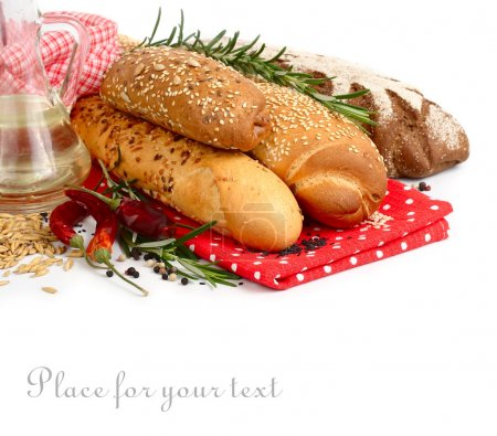 Fresh home-made bread and rosemary on a red napkin on a white background.