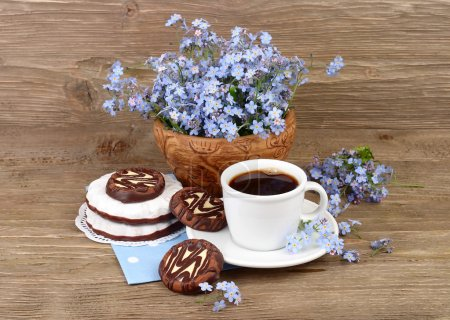 Photo pour Tasse de café frais parfumé avec des biscuits et un bouquet de champs oubliés sur un fond en bois . - image libre de droit