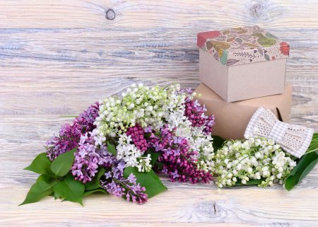 "Photo for Bouquets of a lilac and lilies of the valley and gift boxes on a wooden background. A background to the subject ""holiday"". - Royalty Free Image"
