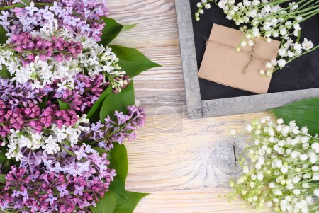 Photo for Flower background with a lilac, lilies of the valley and a cretaceous board with a place for the text. Top view. - Royalty Free Image