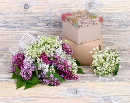 Photo for Flower wooden background with a lilac, lilies of the valley and gift boxes with a place for the text. - Royalty Free Image