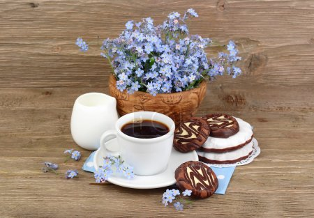 Cup of coffee with cookies and a bouquet of blue wild flowers on a wooden background with a place for the text.