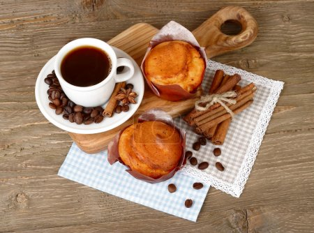 Cup of coffee with cakes and coffee grains on a wooden background. Top view.