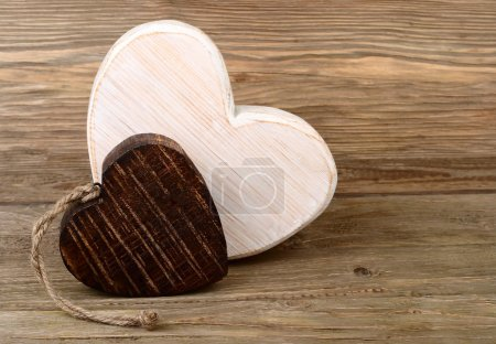 "Two wooden hearts on a wooden background. A background for the subject ""love""."