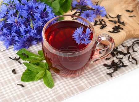 Transparent glass cup of black tea with mint and cornflowers on a white background.