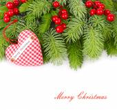 Fluffy branches of a Christmas tree, textile heart and red berries on a white background. A Christmas background with a place for the text.
