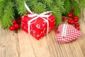 Piros ajándék doboz, piros bogyós gyümölcsök és a fából készült háttér piros kockás textil szív. A karácsonyi háttér a hely, a szöveg