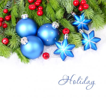 Blue Christmas balls and stars and red berries on fluffy branches of a Christmas tree on a white background. A Christmas background with a place for the text.