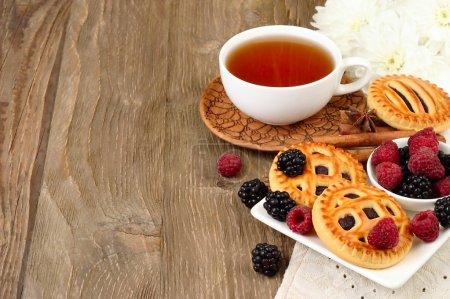 Cup of black tea, berry cookies and fresh raspberry and blackberry on a dark wooden background. Horizontal format.