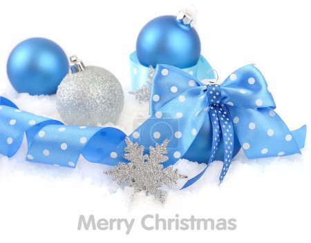 Christmas ball with a blue bow on snow on a white background. A Christmas background with a place for the text.