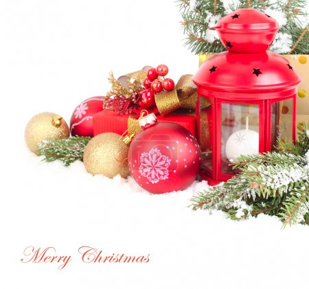 Christmas composition with a red small lamp candlestick and golden and red Christmas balls on snow-covered branches of a Christmas tree on a white background. A Christmas background with a place for the text.