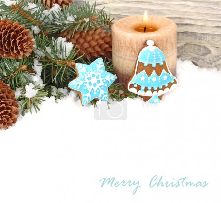 Christmas ginger cookies in blue glaze, nuts and cones on snow on a white background. A Christmas background with a place for the text.