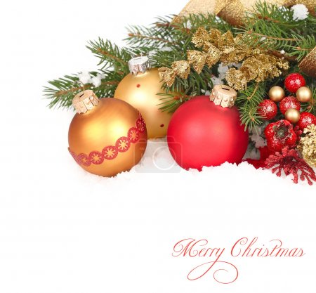 Christmas composition with gold and red Christmas balls and tapes on snow-covered branches of a Christmas tree on a white background. A Christmas background with a place for the text.