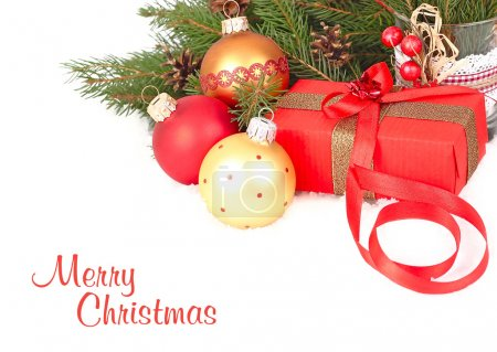Christmas composition with gold and red Christmas balls and a gift box on snow-covered branches of a Christmas tree on a white background. A Christmas background with a place for the text.