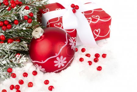 Christmas composition with a red gift box and red berries on snow-covered branches of a Christmas tree on a white background. A Christmas background with a place for the text.