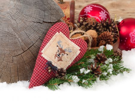 Textile checkered heart with a deer, cones and red Christmas balls on snow on a wooden background. A Christmas background with a place for the text.