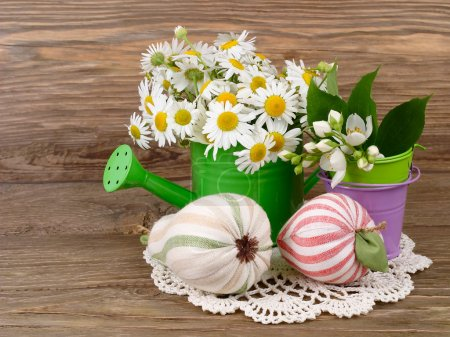 Camomiles in a green watering can and textile decorative apple and a pear on a wooden background. A summer flower background with a place for the text.