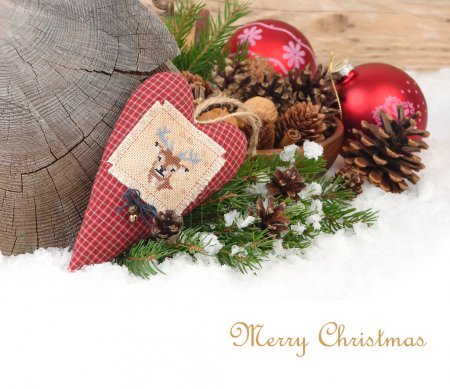 Textile checkered heart with a deer and Christmas balls on snow on a wooden background. A Christmas background with a place for the text.