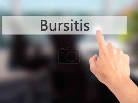 Bursitis - Hand pressing a button on blurred background concept