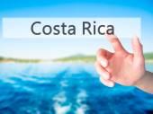 "Постер, картина, фотообои ""Коста-Рика - рука, нажатия кнопки на размытым фоном приготов"""