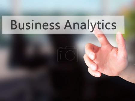 Business Analytics - Hand pressing a button on blurred backgroun