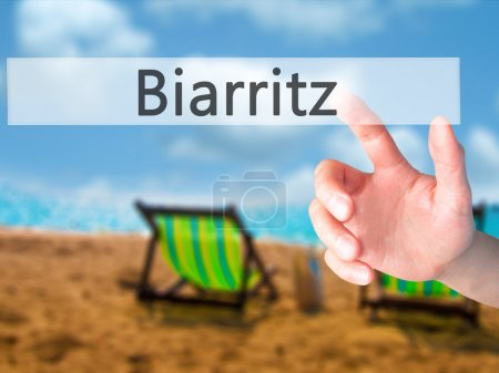Biarritz - Hand pressing a button on blurred background concept