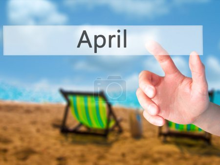 April - Hand pressing a button on blurred background concept on