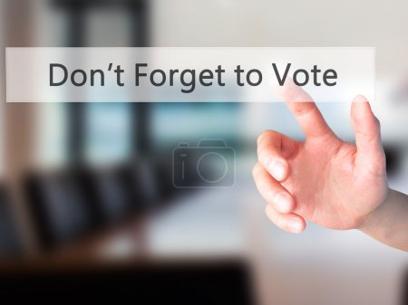 Don't Forget to Vote - Hand pressing a button on blurred backgro