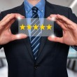 Businessman holding five star rating - Stock Image. For different background please check my portfolio.