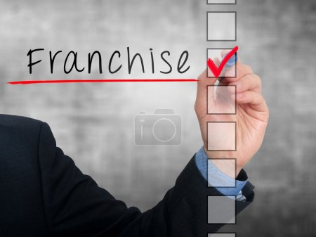 Businessman hand writing Franchise and check listing task. Isolated on blue, grey, ofice background. Stock photo
