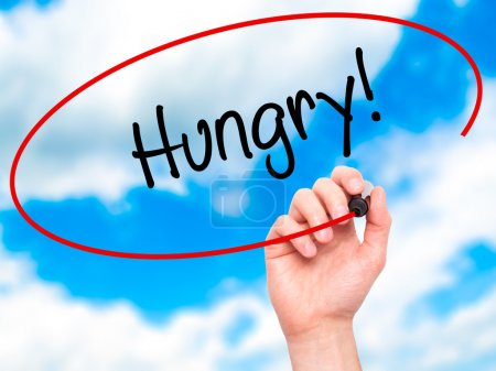 Photo for Man Hand writing Hungry! with black marker on visual screen. Isolated on sky. Business, technology, internet concept. Stock Photo - Royalty Free Image