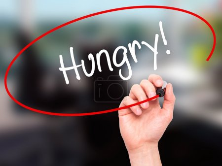 Photo for Man Hand writing Hungry! with black marker on visual screen. Isolated on office. Business, technology, internet concept. Stock Photo - Royalty Free Image