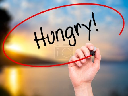 Photo for Man Hand writing Hungry! with black marker on visual screen. Isolated on nature. Business, technology, internet concept. Stock Photo - Royalty Free Image
