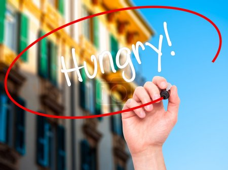 Photo for Man Hand writing Hungry! with black marker on visual screen. Isolated on city. Business, technology, internet concept. Stock Photo - Royalty Free Image