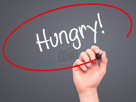 Photo for Man Hand writing Hungry! with black marker on visual screen. Isolated on grey. Business, technology, internet concept. Stock Photo - Royalty Free Image