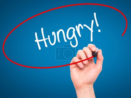 Photo for Man Hand writing Hungry! with black marker on visual screen. Isolated on blue. Business, technology, internet concept. Stock Photo - Royalty Free Image