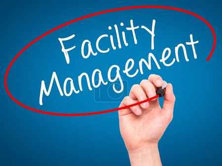 Man Hand writing Facility Management with black marker on visual