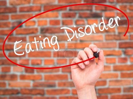 Photo for Man Hand writing Eating Disorder  with black marker on visual screen. Isolated on background. Business, technology, internet concept. Stock Photo - Royalty Free Image