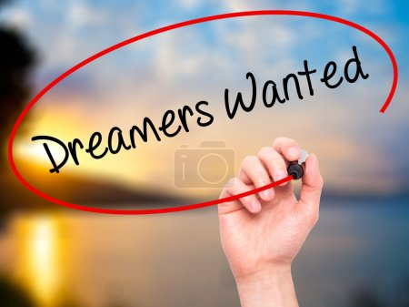 Man Hand writing Dreamers Wanted  with black marker on visual sc