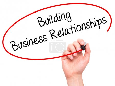 Man Hand writing  Building Business Relationships  with black ma