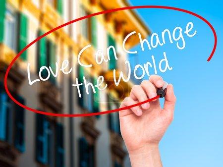 Photo pour L'homme Écriture à la main L'amour peut changer le monde avec un marqueur noir sur l'écran visuel. Isolé sur fond. Affaires, technologie, concept internet. Photo de stock - image libre de droit