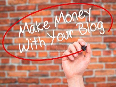 Photo pour Homme écriture à la main Gagnez de l'argent avec votre blog avec marqueur noir sur l'écran visuel. Isolé sur briques. Affaires, technologie, concept internet. Photo de stock - image libre de droit
