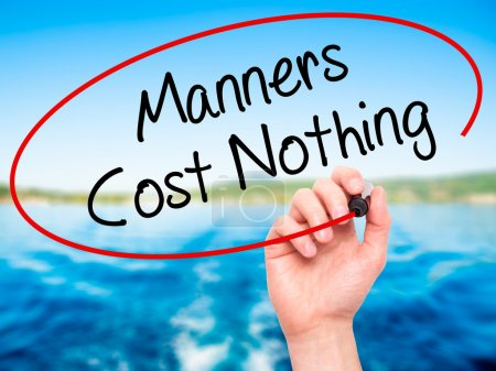 Photo for Man Hand writing Manners Cost Nothing with black marker on visual screen. Isolated on nature. Business, technology, internet concept. Stock Photo - Royalty Free Image