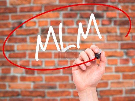 Photo pour Homme écriture manuelle MLM (Multi-Level Marketing) avec marqueur noir sur l'écran visuel. Isolé sur fond. Affaires, technologie, concept internet. Photo de stock - image libre de droit