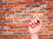 Man Hand writing Together Everyone Achieves More with black mark