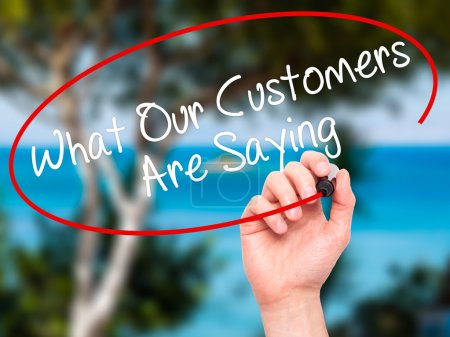 Man Hand writing What Our Customers Are Saying with black marker